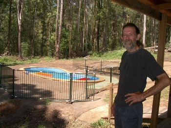 Romney proudly stands near his new swimming  pool