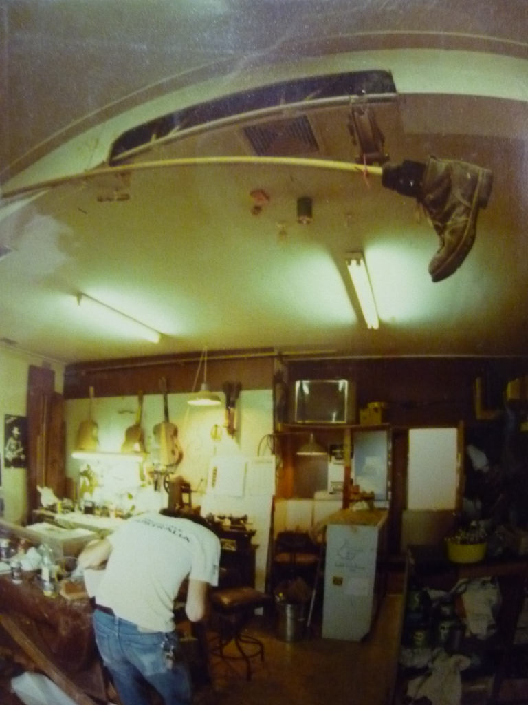 Romney Godden at work 1982 with 'the boot' hanging precariously above. The boot was made by Rommo and Greg and was inspired by similar whacky things in Bugs Bunny cartoons. Yes, it did get used on a few choice occasions when mistakes were made...